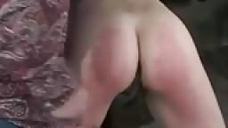 Une jeune soumise se prend des coups de baguettes et des coups de fouets