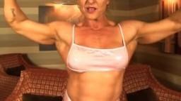 Femme bodybuilder montre ses muscles au fur et à mesure qu'elle se déshabille