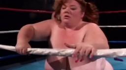 Une grosse femme baisée sur un ring par une naine avec un gode ceinture - Film x