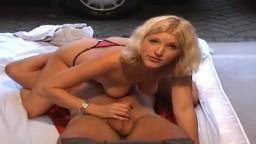 Une hollandaise en 69 sur le sol d'un garage avec la porte grande ouverte sur la rue - Film porno