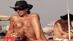Une nudiste filmée par un voyeur fait une bronzette nue sur la plage
