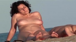 Une sympathique milf nudiste espionnée par un voyeur sur la plage