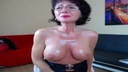 Une femme mature avec des gros seins siliconés se masturbe sur le web