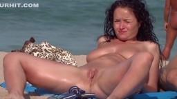 Cette fille naturiste a les jambes grandes écartées sur la plage