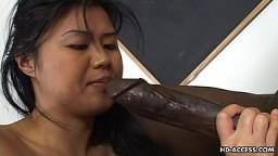 Une jeune asiatique se prend une énorme bite black dans la chatte
